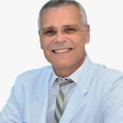 foto do rosto do dr leonidas varella senhor de cabelo branco óculos e gravata sorrindo