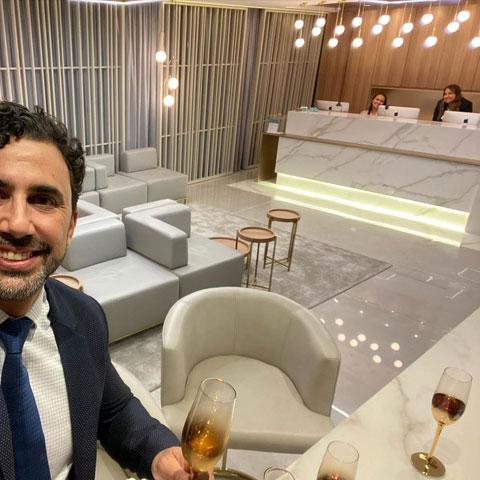 doutor roberto chacur com taça de champagne na mão tira selfie na recepção com atendentes sentadas ao fundo sofá central e poltronas ao redor da sala em tons de branco e dourado