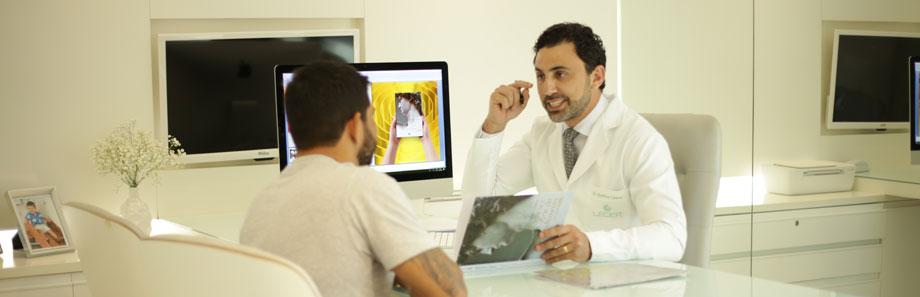 médico sentado no consultório explica as possibilidades da harmonização facial ao paciente