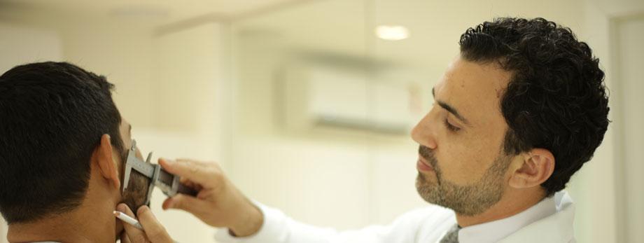 médico marca rosto de paciente com lápis em consulta de avaliação
